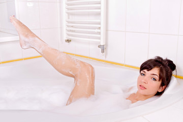 Young brunette woman in the bathtub