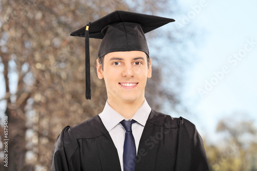 Male college graduate posing outdoors