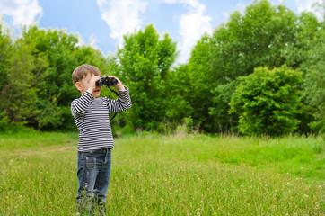 Little boy scanning the woods with binoculars
