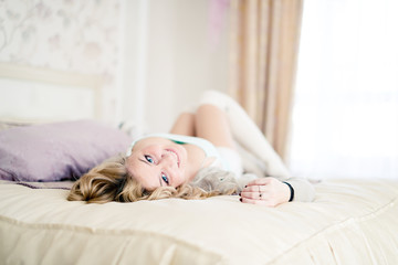 beautiful young blonde woman with long hair smiling and lying on