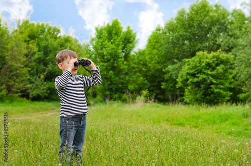 Little boy scanning the woods with binoculars
