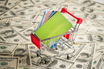 Credit card within shopping cart. Dollar background