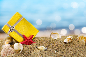 Gold gift box on sand with summer sea background