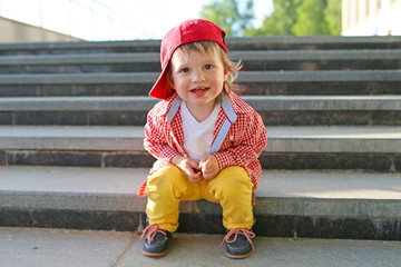 stylish baby sitting on stairs in summer
