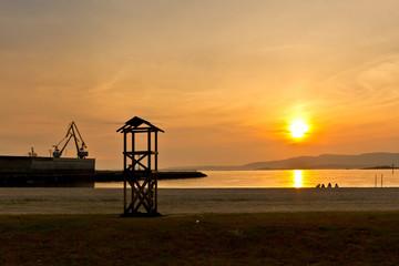 Beach an harbor at sunset