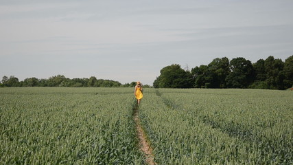 back view of woman with yellow dress walking across rye path