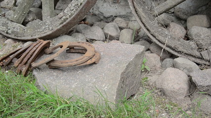 Hand demolish bunch of stacked retrorusty horse shoes on stones