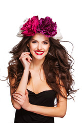 sexy happy model with curle hair and bright peonies on her head.