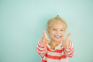 cheerful girl lifts thumb upwards