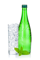 Glass of water with ice, bottle and mint