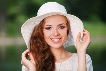 Portrait of pretty cheerful woman wearing white straw hat in
