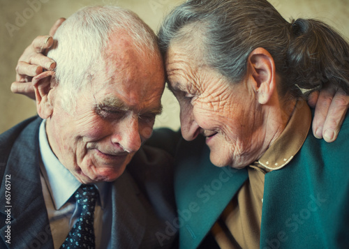Cute 80 plus year old married couple posing for a portrait - 65765712
