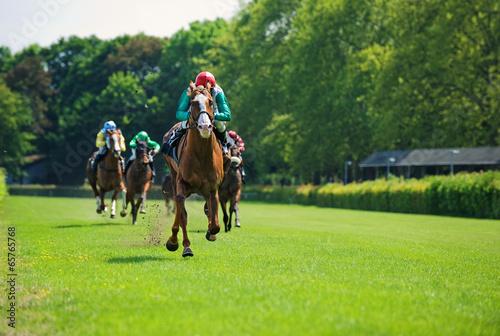 Tuinposter Paardensport Rennpferde mit Jockeys auf der Zielgeraden