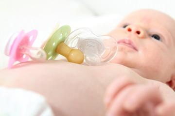 Baby mit verschiedenen Schnullerformen auf Brust