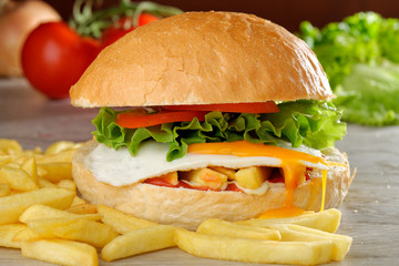 Big veggie burger with egg, fresh vegetables and french fries