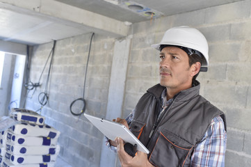 Construction manager using tablet on building site