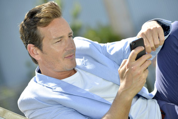 Man relaxing outside and using smartphone