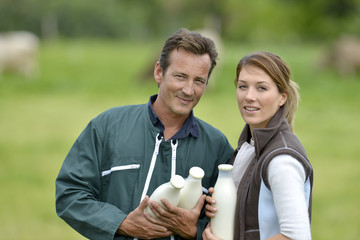 Couple of farmers in field holding milk bottles