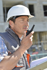 Man on building site using walkie-talkie