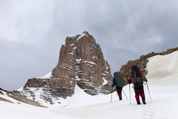 Two hikers in snowy mountains before storm