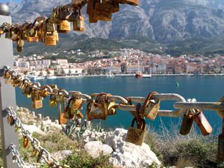 Love padlocks with mediterranean city in background