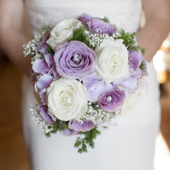 closeup bride holding bouquet of roses