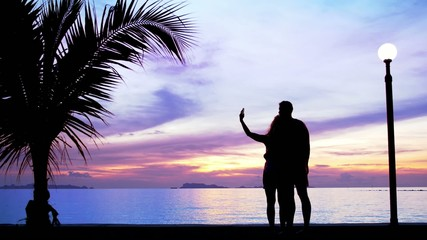 Silhouettes of couple in love make selfie against sunset