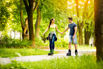Young sporty couple ride rollerblades