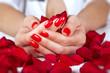 Obrazy na płótnie, fototapety, zdjęcia, fotoobrazy drukowane : Red manicure on a woman hands with leafs of roses.