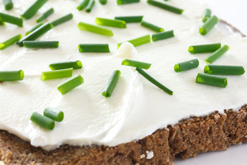 Cut fresh chives on thickly spread cream cheese on bread.