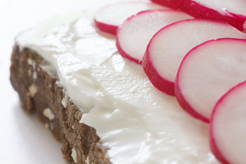 Thinly sliced radish on thickly spread cream cheese on bread.