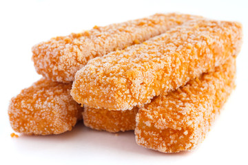 Frozen bread crumbed fish fingers on white