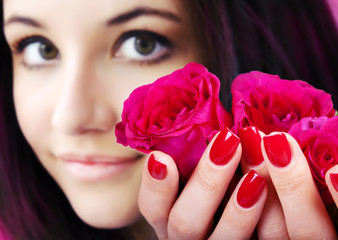 Red manicure on a woman hands with red roses.