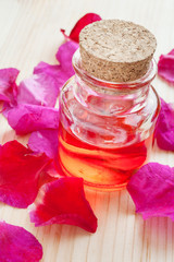 oil in glass bottle and rose petals