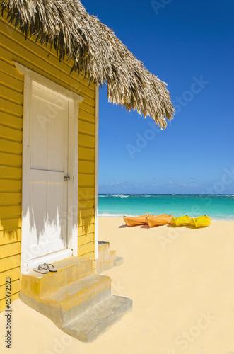 Papiers peints Amérique Centrale Wooden yellow beach cottage against colorful kayaks
