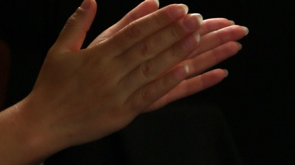 Female hands applaud on a black background, close up