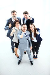 Top view of successful young business people showing thumbs up