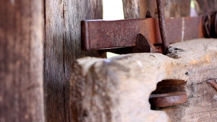 Female hand closes old wooden door with an iron latch