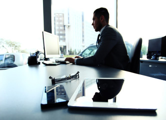 Silhouette of businessman using laptop in office