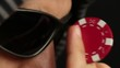 Poker player adjusting his sunglasses with a red chip, close up
