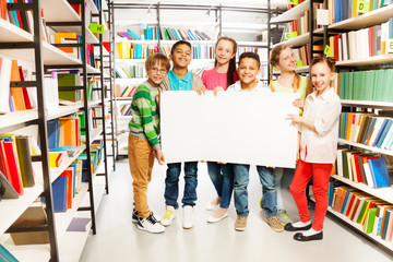 Kids holding white paper sheet in library