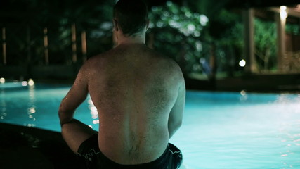 Man sitting next to pool at night, steadycam shot