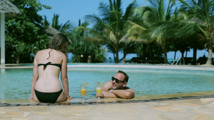 Couple talking and drinking in swimming pool, steadycam shot