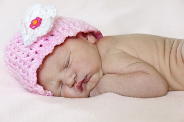 Closeup of newborn baby sleeping with pink knit hat