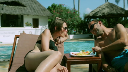 Couple feeding each other in swimming pool, steadycam shot