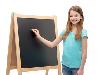 happy little girl with blackboard and chalk