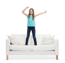 smiling little girl jumping or dancing on sofa