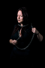 portrait of beautiful girl tied in chains on black background