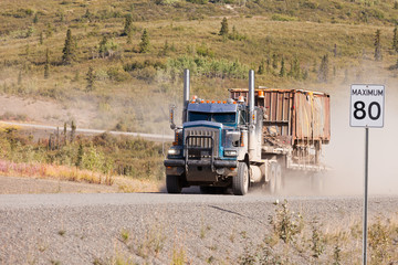Industrial truck driving dusty rural dirt road