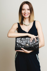 Elegant outfit. Stylish woman with black handbag